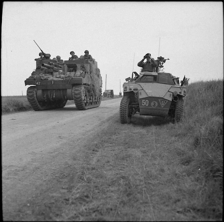 Priest self-propelled gun passes a Humber scout car