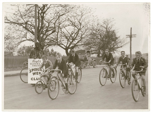 """Boys of Hoyts Clovelly Theatre """"Spider's Web"""" Club ride their bikes while """"Spiderman"""" looks on, by Sam Hood 