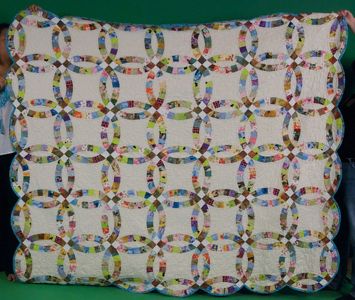 Okay, so we didn't totally hold it straight, but that's okay ... you get the idea. Much of the humor in this quilt can't be seen from this angle -- you don't see all the weird and funny pieces (pink and black skulls! backing fabric of cartoony bugs!) but this at least lets you see the overall effect. A traditional quilt done in as non-traditional a manner as possible!  Blog entry: domesticat.net/quilts/serendipity