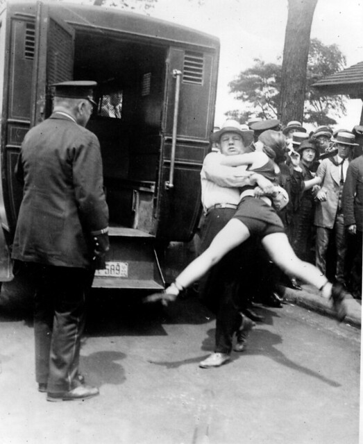Man struggling to put a young woman in the back of a police wagon