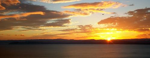 ocean sunset sea newzealand sun water clouds plane airplane flying aeroplane hills flare gisborne kaitihill
