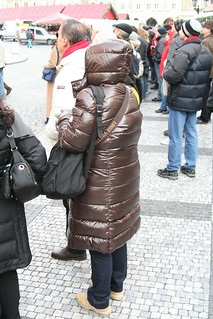 Italian woman in shiny Moncler downcoat hood up in cold Prague