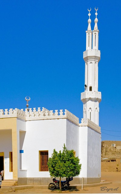 Modern mosque with minaret in contrast to the next one