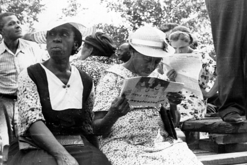 """Photo verso reads """"Union meeting - reading is not easy.""""  An unidentified woman and Sylvia Lawrence read the """"Sharecroppers' Voice"""" during an outdoor STFU meeting 