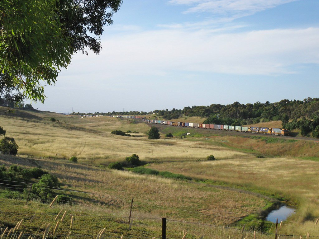 Nearing the end of its cross country journey, train #PM5 rolls downhill along the outskirts of Geelong by Adam Serena