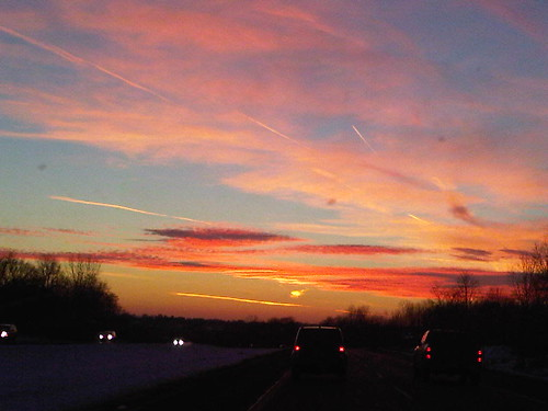 Tail lights, contrails and sunset sky