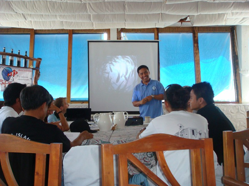 Photo of a group of staff at a dive centre learning about the environment during a Green Fins awareness raising session. The staff are seated at a table and the presenter is smiling with a photo of abundant marine life on the screen behind him.