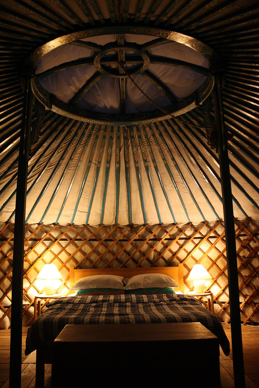 Image of modern glamping abode inside a traditional yurt imbuing glampers staying in accommodation with cultural immersion and historic connection.