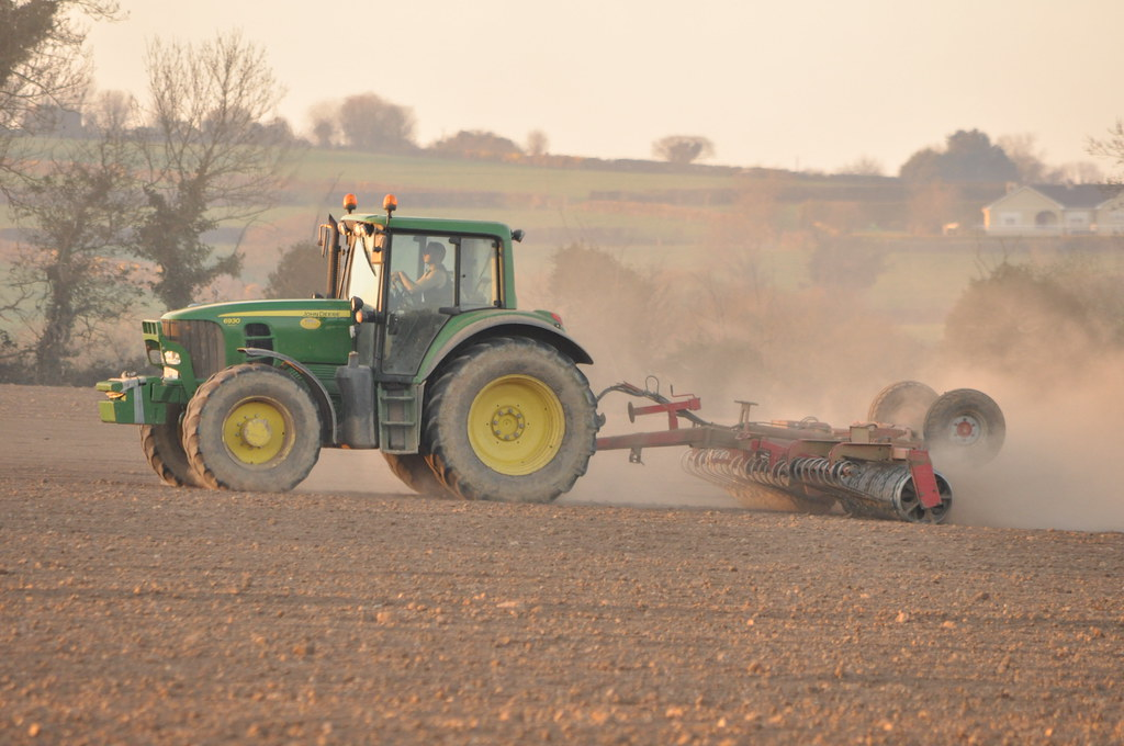 john deere 6930 tractor with a heva tiproller  a word