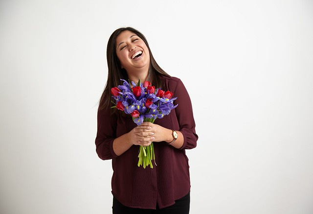 happy woman holding bouquet of red tulips and blue irises