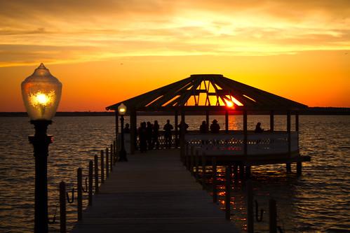 sunset sky people sun water lamp beautiful spectacular golden bay amazing calm gazebo deck lamppost admire