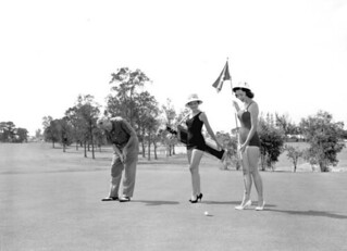 Golfer with bathing beauties as caddies during the Tri-County Suncoast Festival: Dunedin, Florida