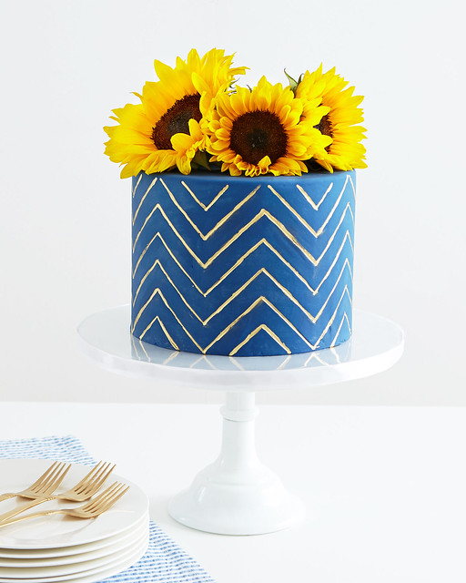 potted sunflower on blue and white zig zag pattern frosted cake on white stand with plates and forks