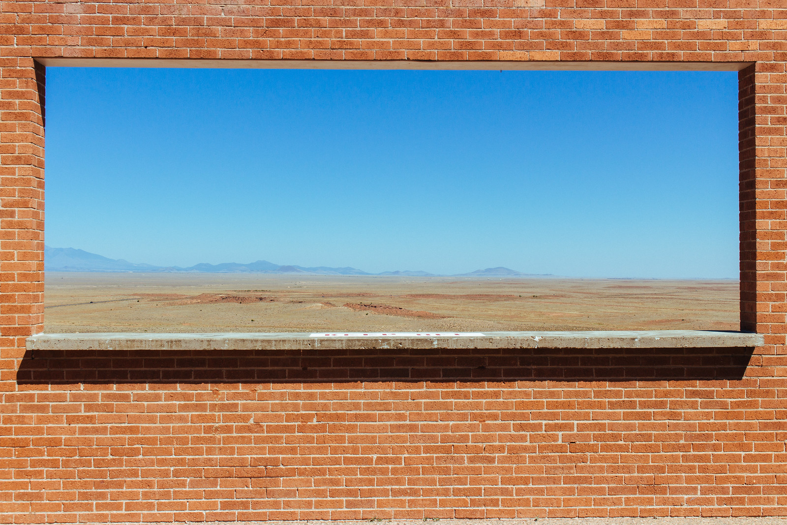 Desert, mountains, and blue sky seen through a brick window in Arizona