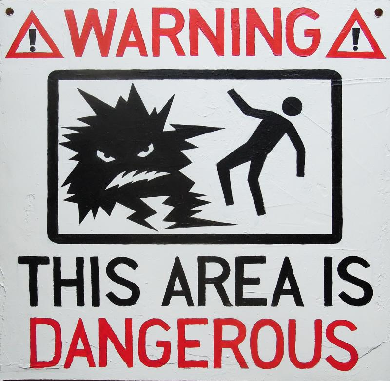 """A white hazard sign with an image of a human stick figure being sapped by a electric blob. Image is sandwiched between red and black text - """"Warning, this area is dangerous"""""""