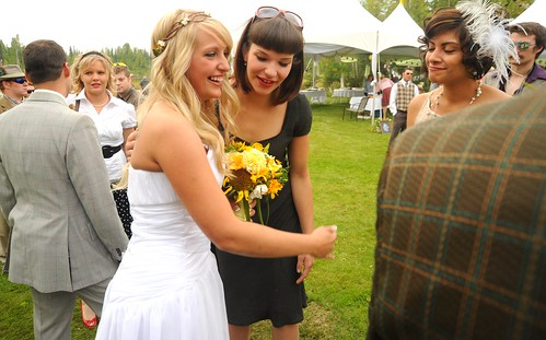 Mrs. Jessie Morse, wearing her white wedding dress, next to her groom Chris, smiling holding a bouquet and talking with friends, Sophia Isabel, Travis Olsen (wearing the tweedy plaid on the right out of frame), Fairbanks, Alaska, USA   by Wonderlane