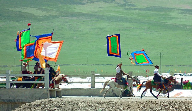 Flag bearers riding at speed to Sershul temple, Tibet 2014