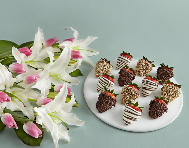 white lilies and pink tulips with Shari's Berries dipped strawberries with nuts and chocolate chips