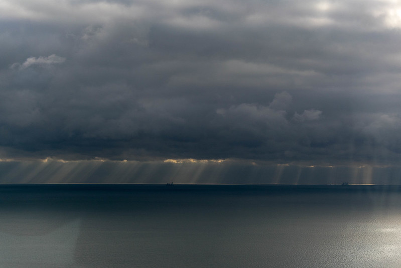 Boats at the horizon while the sun tries to break through the clouds