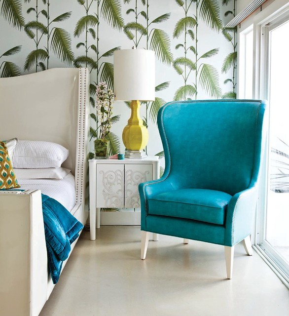 Bedroom with turquoise chair, palm wallpaper, yellow lamp