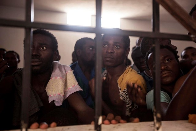 Sub-Saharan illegal migrants and refugees are pictured begging for their release in one Surman detention centre. The centre's director (not pictured) stands in front of the cell, threatening to beat them with a stick if they do not calm down. The detainees freeze in panic. Surman, Libya.