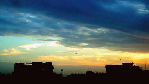 blue houses homes sunset sky orange sun white silhouette clouds dark teal deep indigo cloudysky tasmiahsphotostream