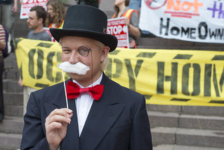 Protester plays role of a banker at rally to demand accountability from the financial institutions   by Fibonacci Blue