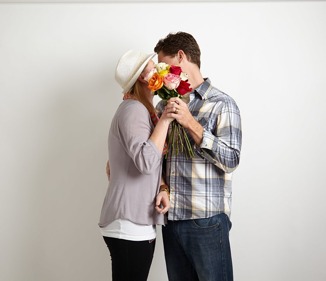 kissing man and woman with bouquet of assorted multi-color roses