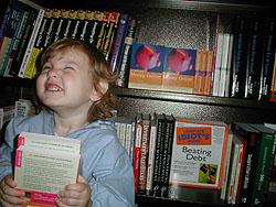 Athena, as a toddler, holding a couple copies of my book in the bookstore.