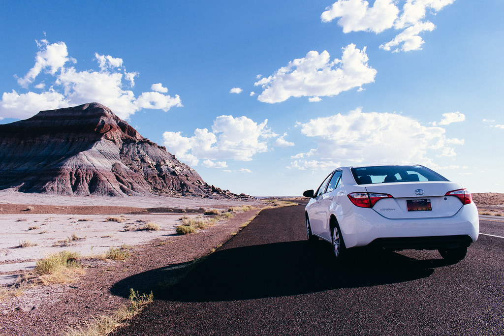 A white Toyota Corolla sedan is parked on asphalt next to an eroding butte with alternating layers of gray and brown soil