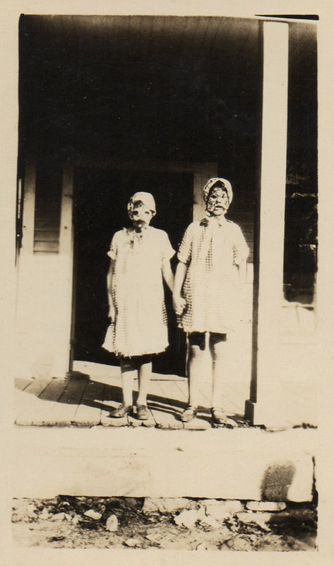 Two girls in Halloween masks on a porcch