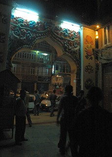 Night's neon lights over Boudha's front gate, taxis waiting for fares, eight auspicious symbols, wish fulfilling jewels, apartment building and restaurant beyond, Boudha, Kathmandu, Nepal