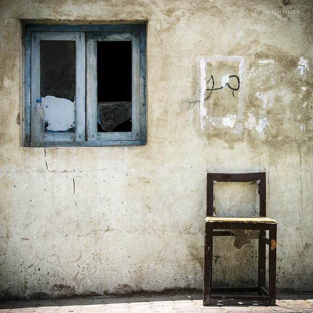 window, bottle & an empty chair