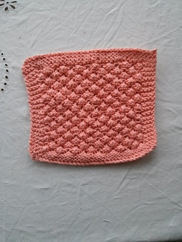 A pink square dishcloth in a knitted, textured raspberry stitch pattern with garter border.