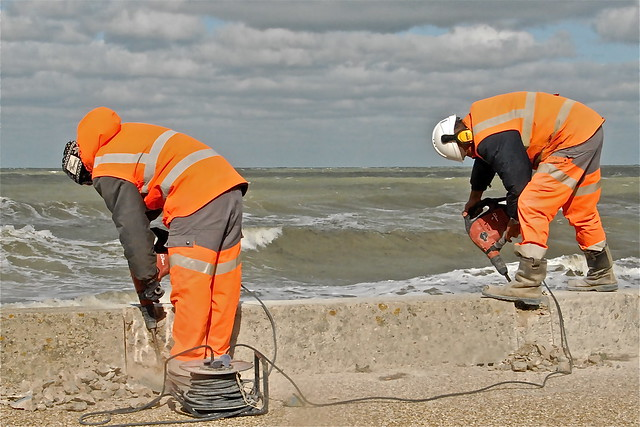MEN AT WORK ON THE SEAWALL OF:VER SUR MER-NORMANDY-FRANCE 2013