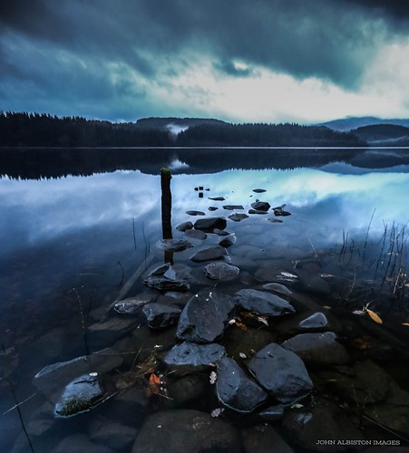 loch ard trossachs scotland moody cloudy misty atmospheric water reflection forest post jetty derelict stones rocks clouds