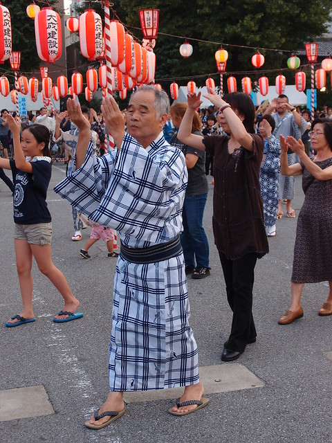 un festival au Japon avec des gens qui tendent leur mains vers le ciel