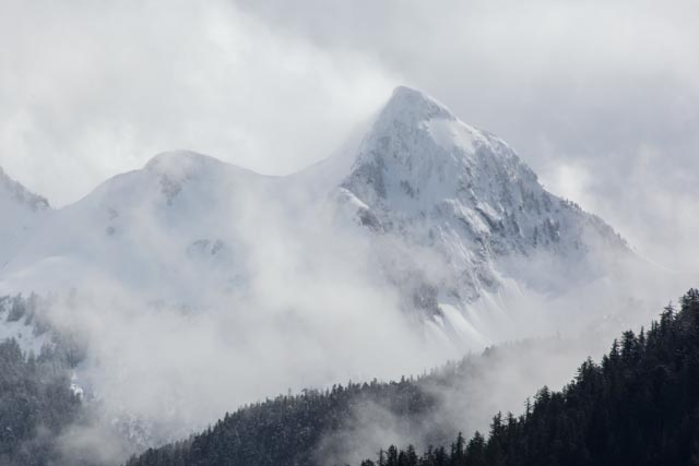 Snow capped peak breaking out of the clouds