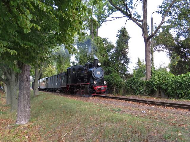 narrow gauge steam locomotive, nearby station