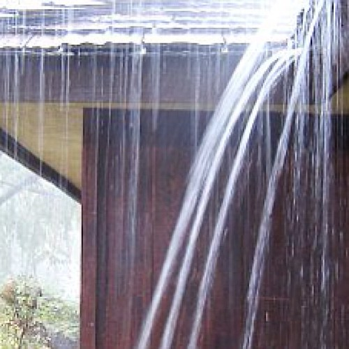 Water Flowing Off A Roof During A Rain Storm With No Gutte