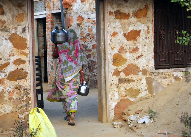 Woman carrying water in small village between Agra and Jaipur, India