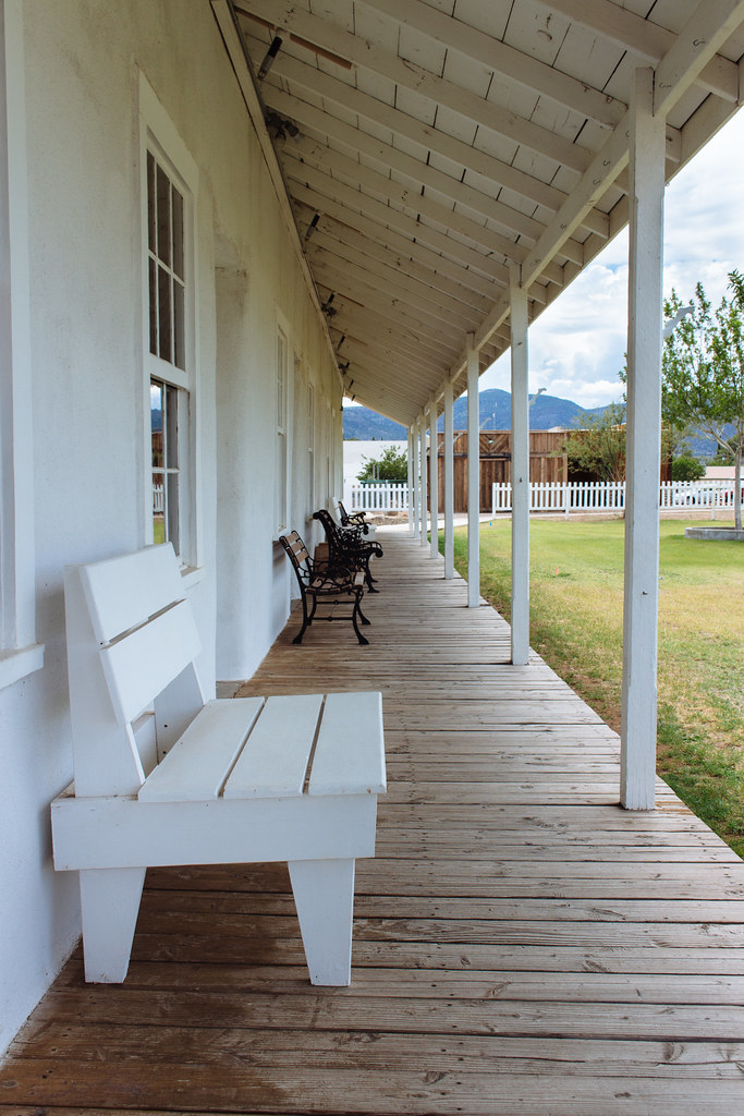 A house's covered porch with benches in front of a grassy lawn