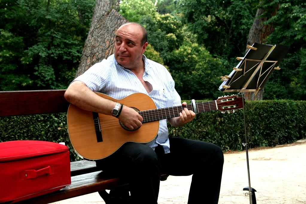 Man playing guitar at El Parque Retiro in Madrid, Spain.