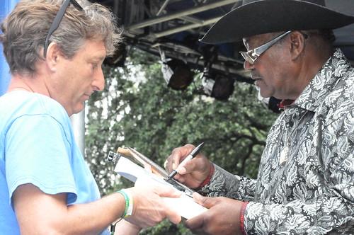 NOJ&HFF's Scott Aiges has Rev John Wilkins signs a guitar at Crescent City Blues & BBQ Fest. Photo by Kichea S Burt.