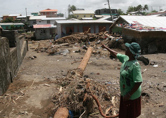 A resident of the Windward town of Black Point, St. Vincent and the Grenadines, points out damage caused to the town by heavy rains on Christmas Eve 2013.