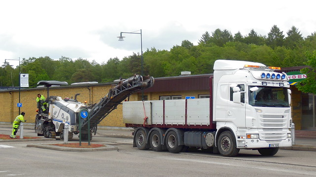 Workers rest while Scania ORW996 Sweden backs up to collect road planings