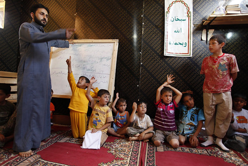 Syrian refugee, Ahmad (far left) teaches a religion class to Syrianrefugee children in the Ketermaya refugee camp | by World Bank Photo Collection