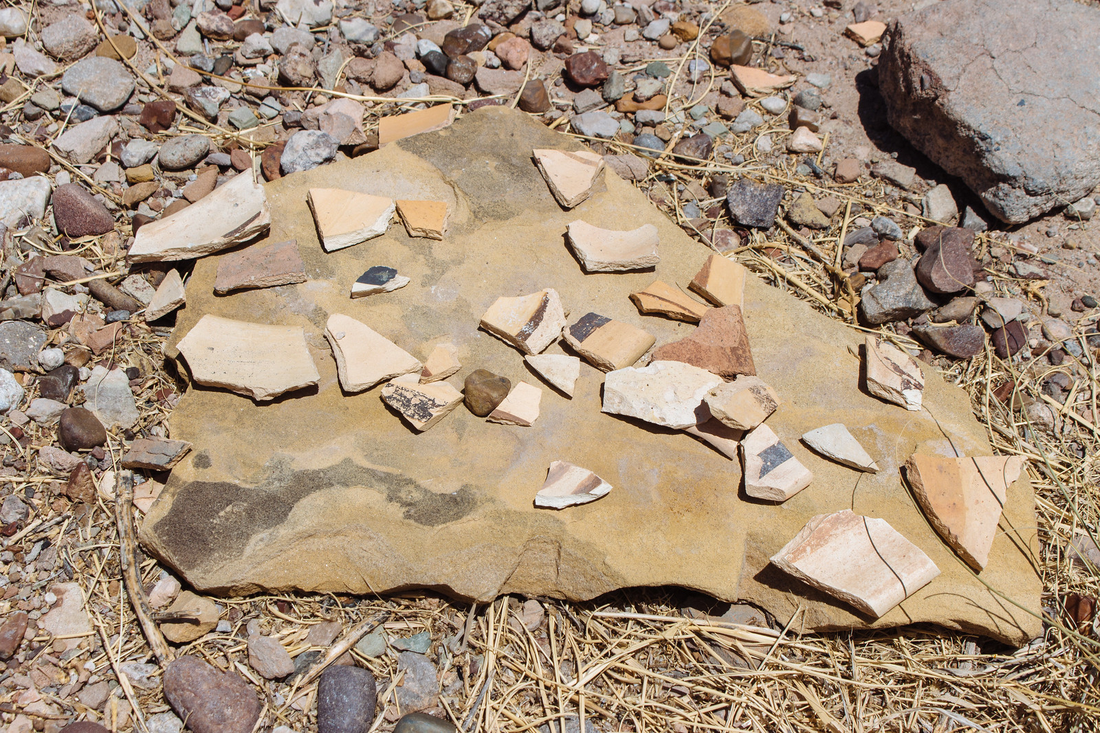Brown yellow and white potsherds with markings on them at Homolovi State Park in Arizona