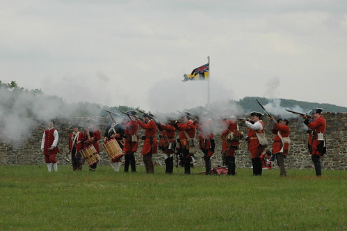 Photo of historic reenactors in British colonial uniforms firing muskets outside Fort Frederick