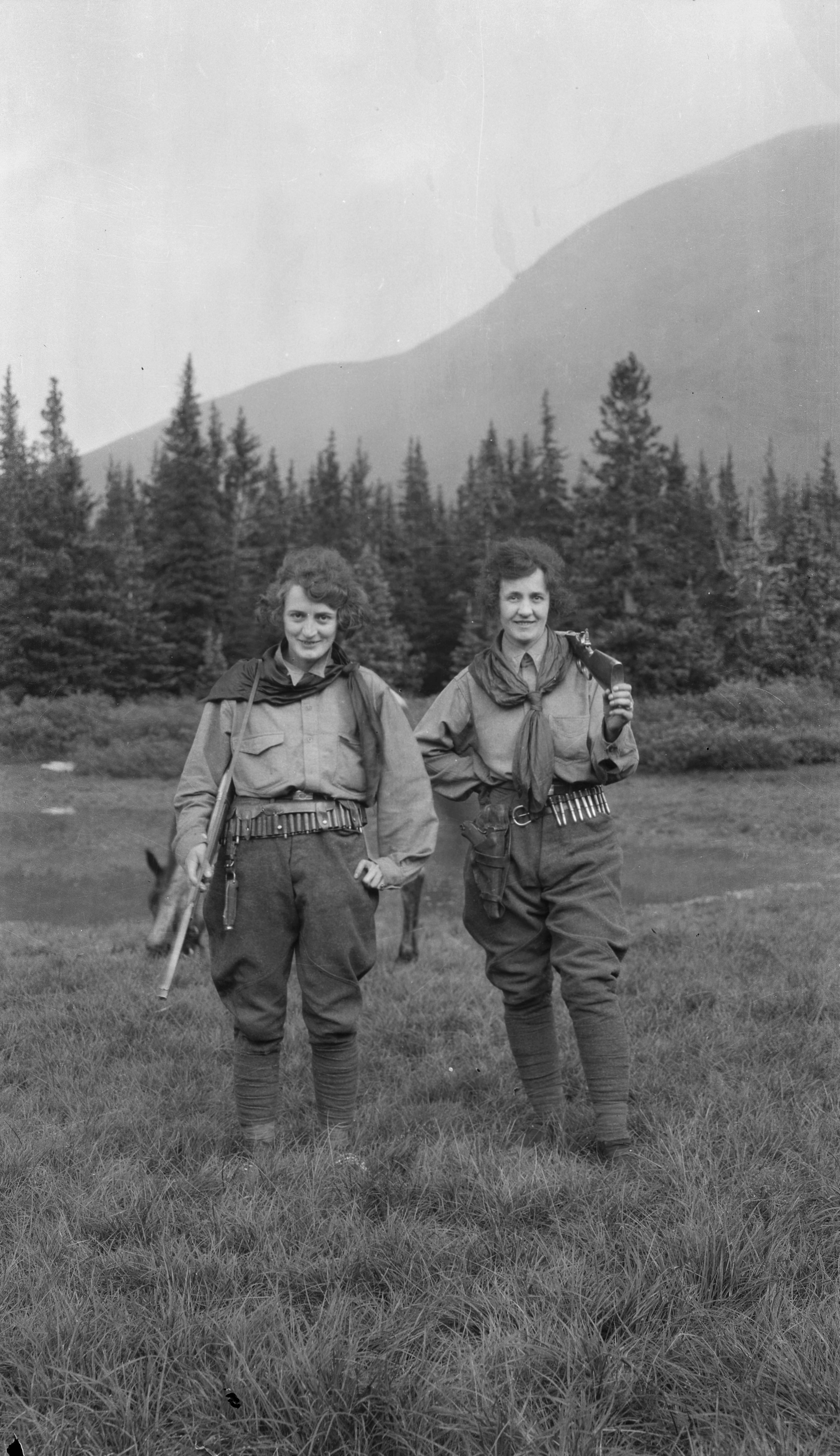 Two women on a trek with rifles and cartridge belts